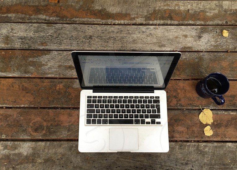 Laptop Apple MacBook Pro on a wood table with a cup of coffee in a autumn atmosphere photo