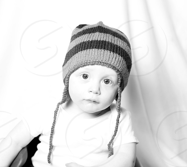 grayscale photo of toddler wearing striped chullo cap photo
