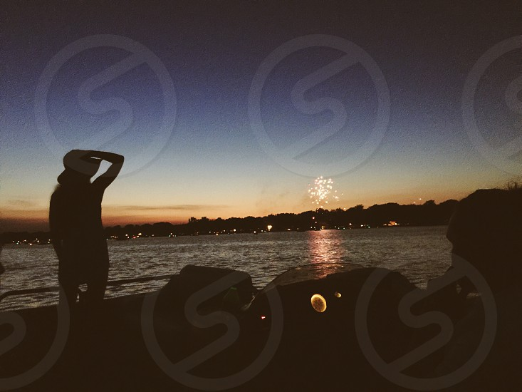 photo of silhouette of a person side body of water near fireworks during nighttime photo