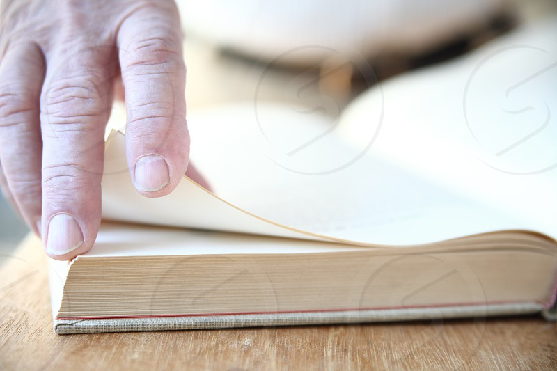 A man turns the pages of a large book. photo