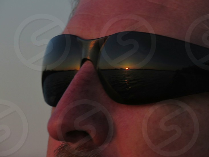 Reasons to travel To see sunset to be in nature to see life in a different light man sunglasses summer reflection of sunset in glasses summer lake dusk partial face close up photo