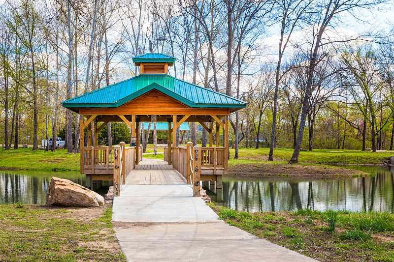 A colorful Gazebo straddles a reflective lake in a city park on a gorgeous spring day with deep green grass a bright blue sky with fluffy white clouds and trees just starting to bud photo