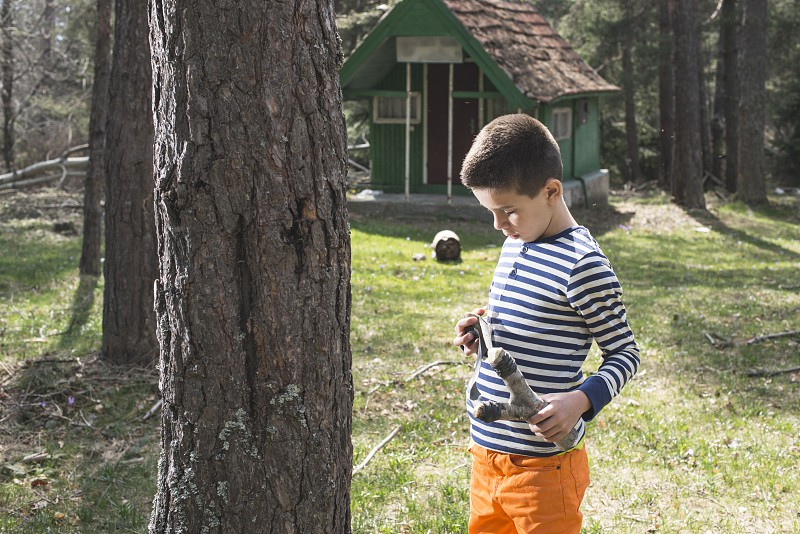Child play with sling toy in the forest. photo