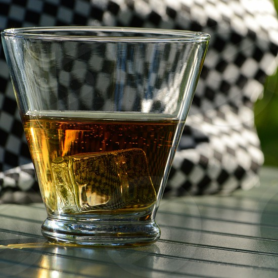 Single whiskey glass with an ice cube and checkered racing flag. photo