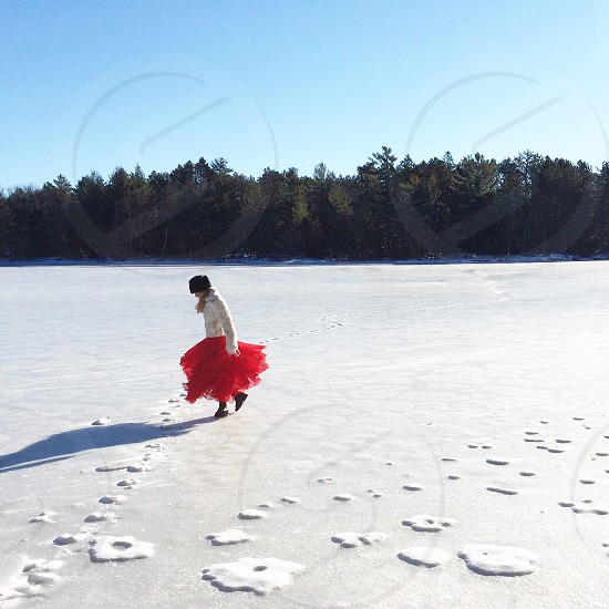 woman in white and red long sleeved dress walking on snow covered ground photo