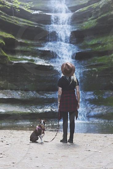 woman in black shirt and pants with black and white dog holding dog leash near waterfalls during daytime photo