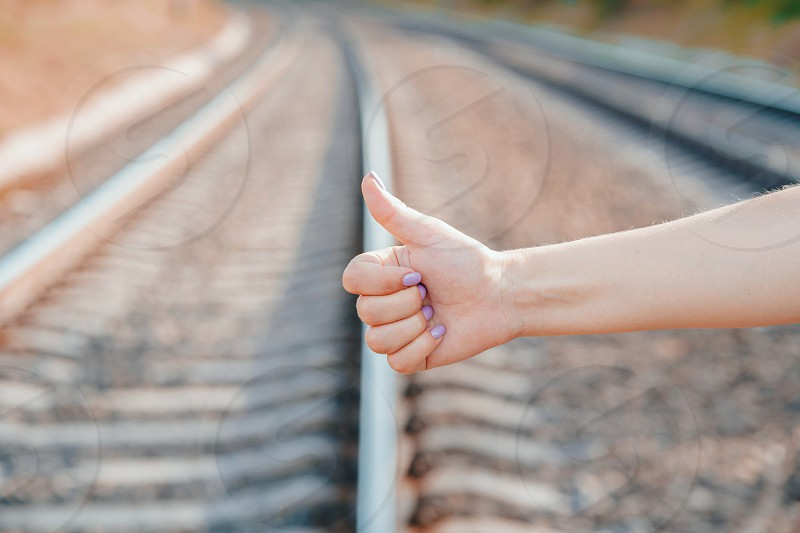 Voting on the railway road. Close up female hand with hitch-hiking gesture. photo