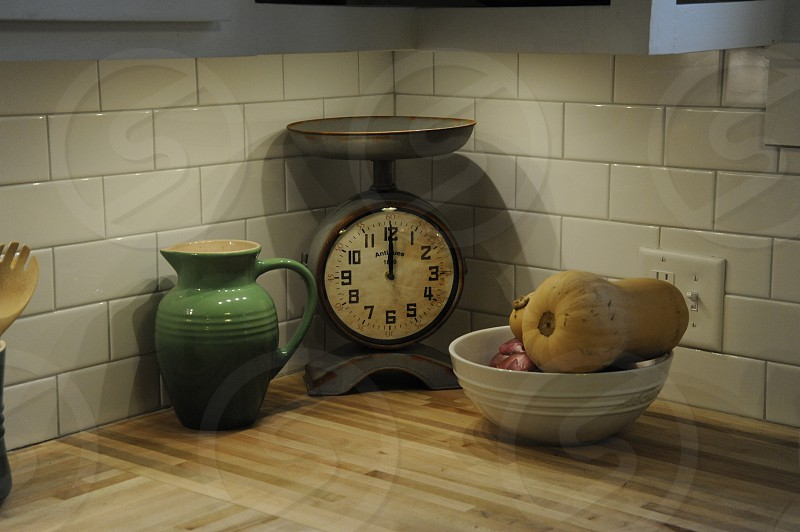 Old scale pitcher and bowl with butternut squash in subway tiled corner of kitchen photo