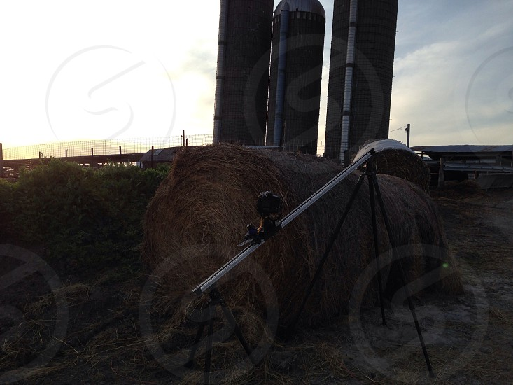 black metal tripod near brown hay photo