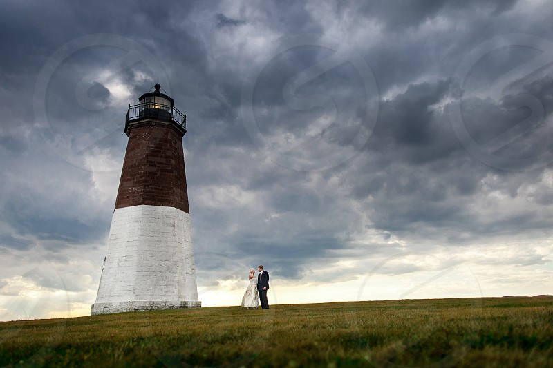 A wedding couple standing at the base of a Rhode Island lighthouse.  Clouds ominous love grass brick New England beach coast. photo