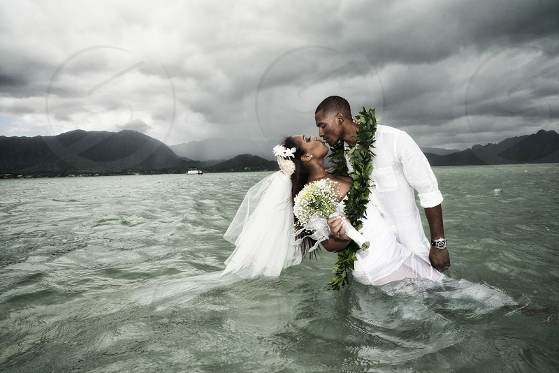 bride and groom kissing in water under grey cloudy sky photo