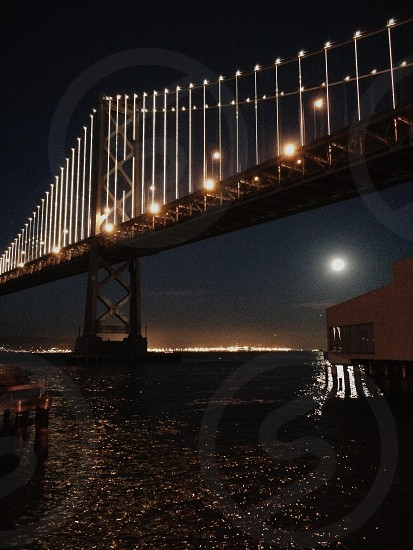 Moonrise under the bay bridge photo