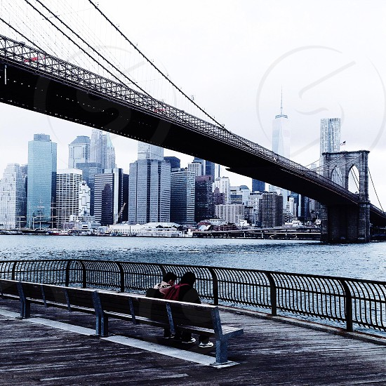two person sitting on bench in front of sea and bridge photo