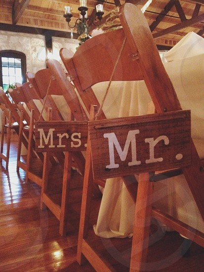 mr. and mrs. wooden boards hanging at the back side part of brown wooden folding chair near white covered clothed buffet table photo