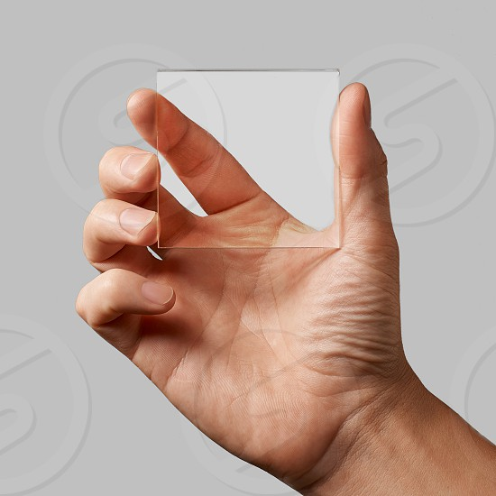closeup of a transparent glass in a man's hands on a gray background copy space for text photo