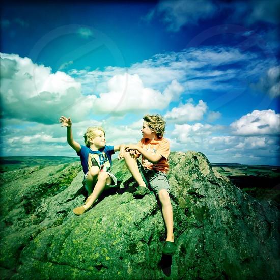 2 boys sitting on rock photo