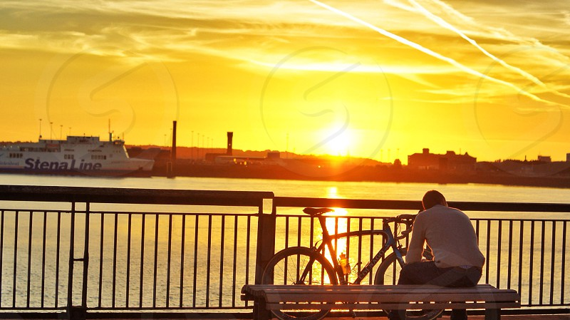man sitting on bench on a pier overlooking sunset photo