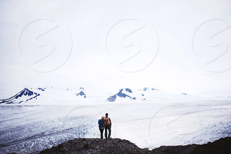 2 people standing on cliff by water during daytime photo