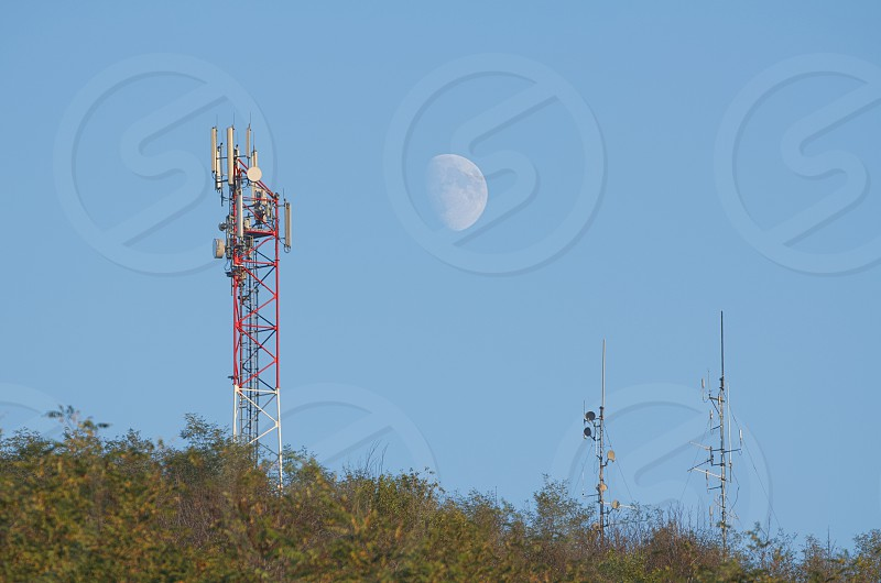 Telecommunications Antennas in the Forest with Clear Blue Sky and the Moon photo