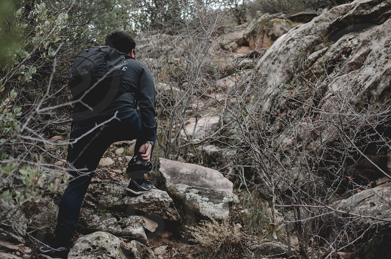 person wearing backpack climbing on rock formation during daytime photo