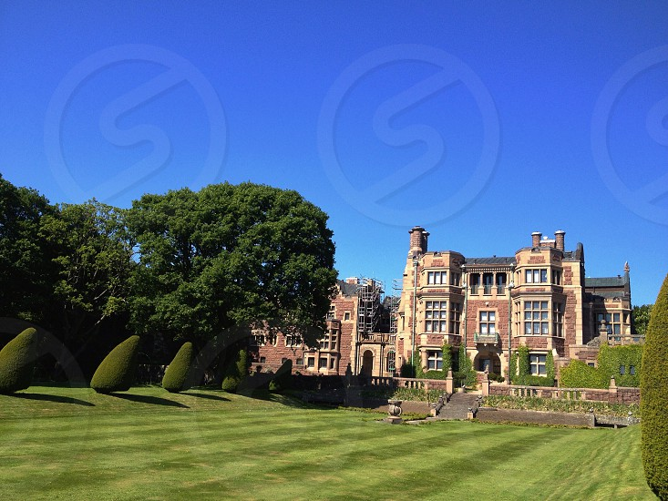 green mowed lawn sculpted hedges red tan stone building clear blue sky photo