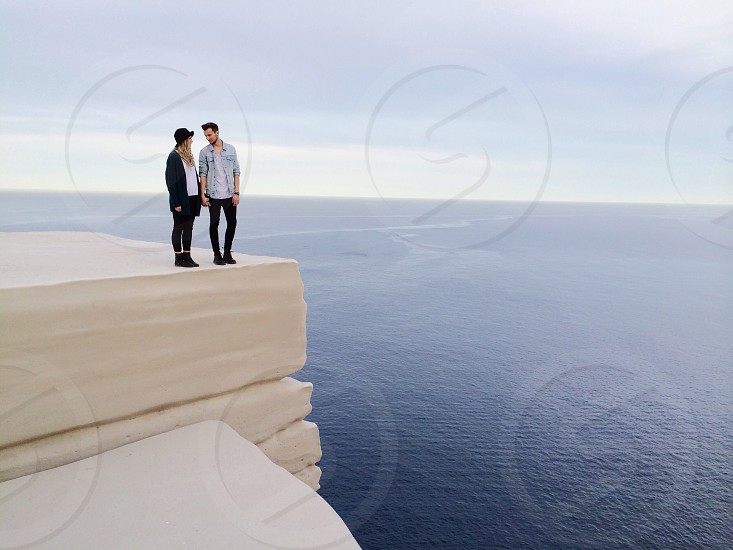 two people on edge of white cliff beside sea under clear sky during daytime photo