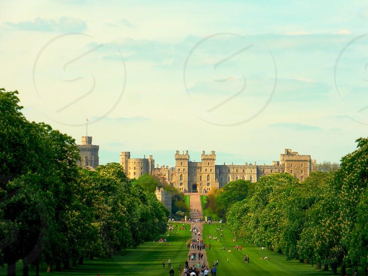 people walking on pathway behind brown castle photo
