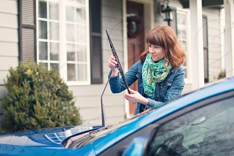 woman wearing blue denim jacket fixing windshield wiper photo