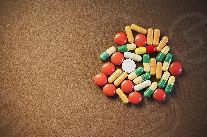 Bunch of various colorful unpacked pills and tablets on brown textured background with empty space on left side of an image.  photo