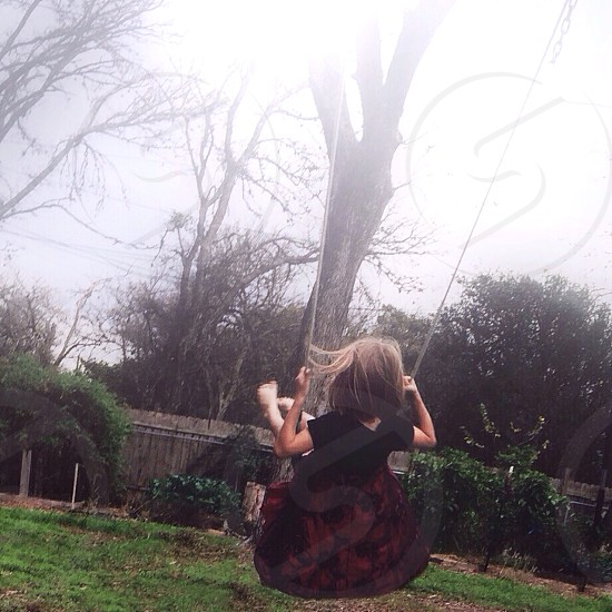 girl in black and red floral dress riding a swing photo