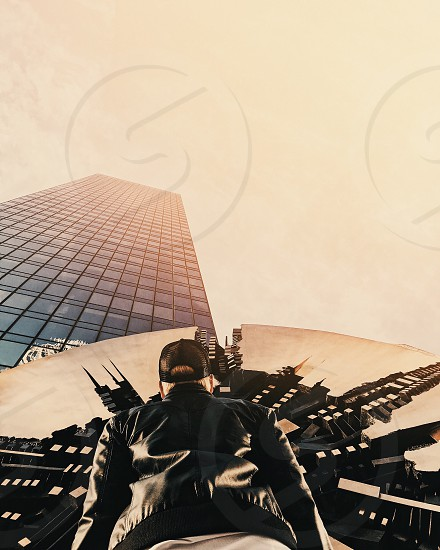worms eye view photography of man in black mesh cap and black leather jacket looking at clear glass high rise city building under blue sky during daytime photo