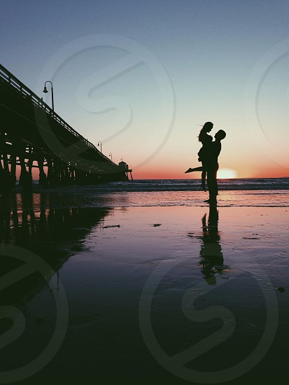 man holding woman up in shallow water photo