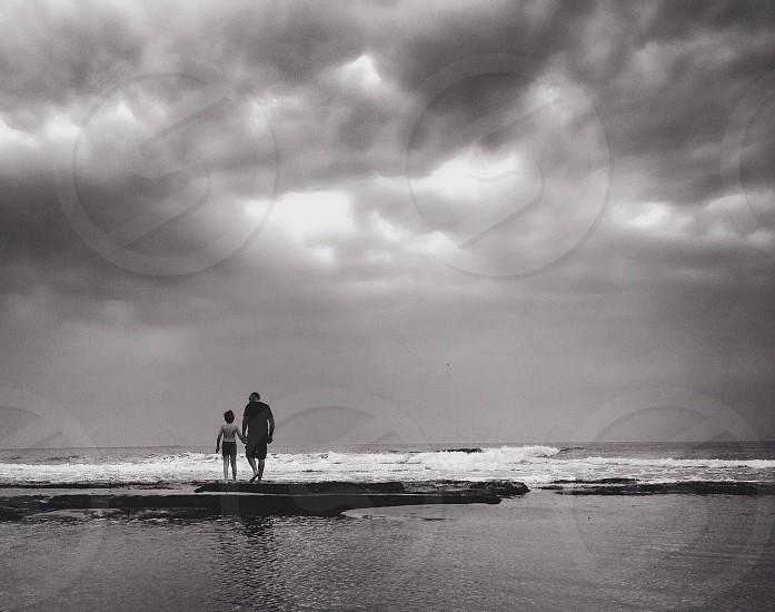 human on seashore and gray clouds photo photo