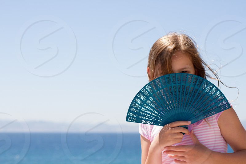 Girl holding Fan with sea in background photo
