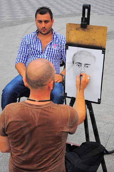 man in brown t shirt sketching man in blue denim jeans photo
