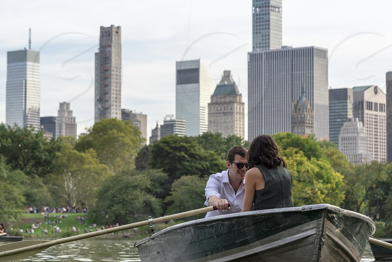 Attractive couple rowing on the lake in Central park with Midtown Manhattan skyline. photo