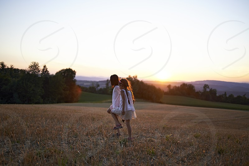 Beautiful magical landscape with two young sisters walking hand in hand during sunset photo