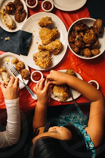 girl sitting at the table eating fried chicken photo
