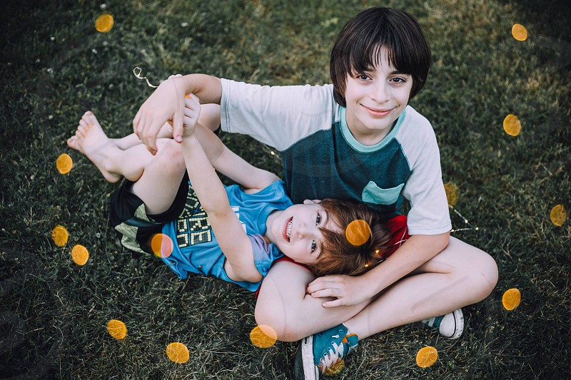 boy and girl sitting on green grass on high angle view photography photo