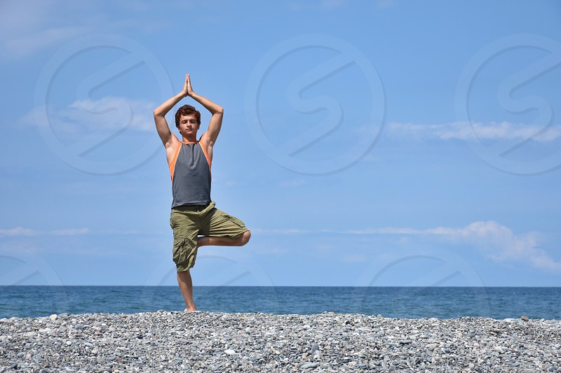 man in gray tank top and green cargo shorts in balancing yoga position on gray beach sand in front blue sea water during daylight photo