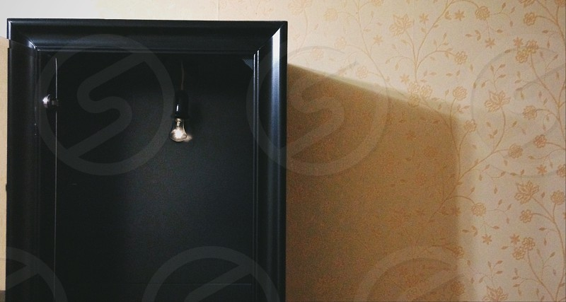 black wooden square frame on beige floral wallpapered wall photo