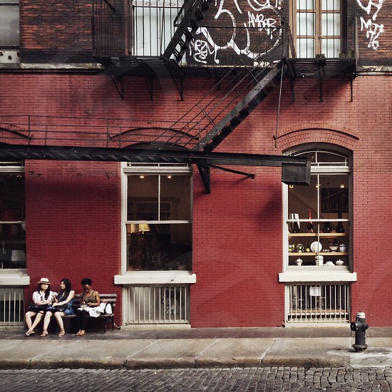 women sitting on bench in front of red brick building photo