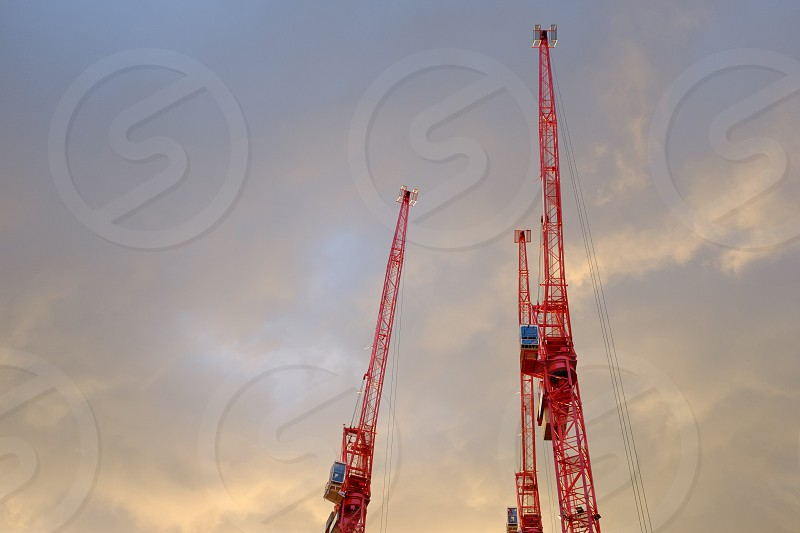 Three red cranes with a cloudy evening sky behind photo