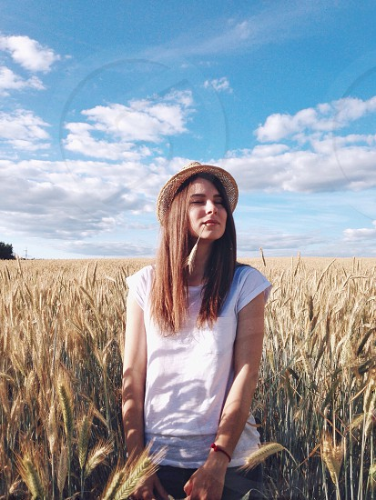 woman with brown long hair in white crewneck shirt standing in wheat field during daytime with cloudy sky photo