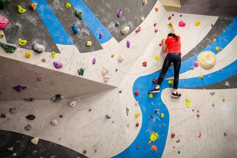 Active young climber woman climbing on indoor climbing wall. photo
