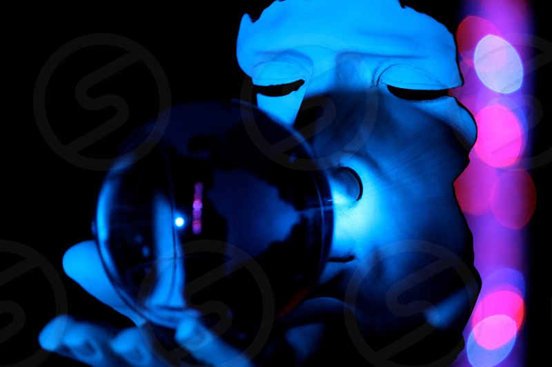 person wearing face mask holding a glass ball in dark photography photo
