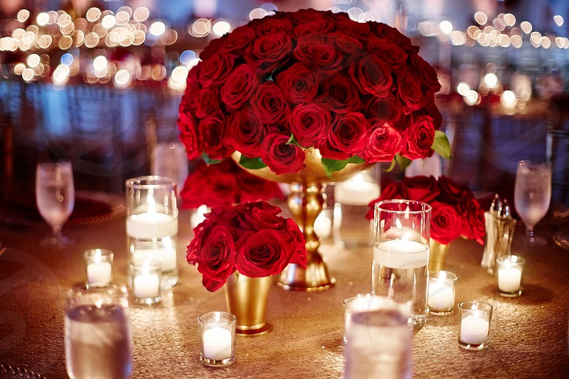 The luxury red roes theme of wedding dinner table decorated with a bunch of red roses in the center and surround with small vase of red roses and candle light. photo