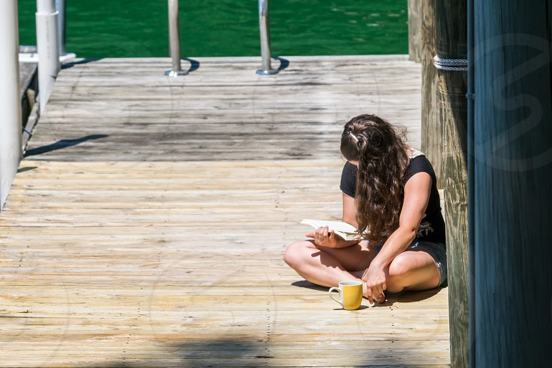 Young girl reading a book on a dock by a lake in the summer sun. photo