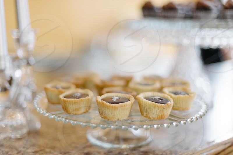 yellow tarts with chocolates on glass tray photo