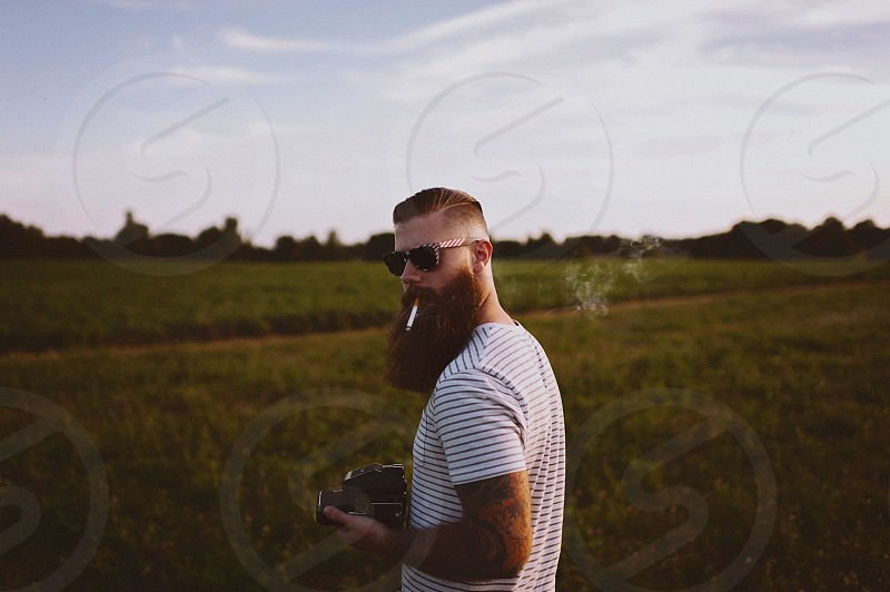 man in t shirt smoking a cigarette in a green field photo